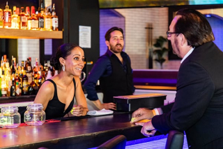 Black and Blue - Bartender helping Customer